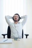 Ontspannen zakenman die aan muziek met hoofdtelefoons luistert Royalty-vrije Stock Foto