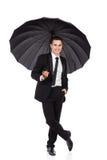 Ontspannen zakenman die zich met open paraplu bevinden Stock Afbeeldingen
