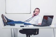 Ontspannen zakenman met benen op de lijst die op de telefoon spreken Stock Fotografie