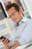 Ontspannen zakenman op kantoor die smartphone gebruiken royalty-vrije stock afbeeldingen
