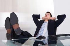 Ontspannen zakenmandagdromen in bureau Royalty-vrije Stock Afbeeldingen