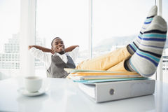 Ontspannen zakenmanzitting als zijn voorzitter met omhoog voeten Stock Foto's