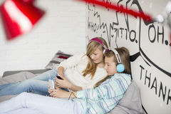 Ontspannen zusters die aan muziek thuis luisteren Stock Foto