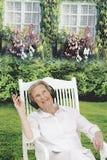 Ontspannende Hogere Vrouw in haar tuin terwijl het luisteren aan muziek royalty-vrije stock afbeelding