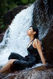 Ontspannende jonge vrouw bij waterval stock foto's