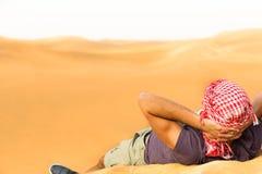 Ontspannende mannelijke toerist die bovenop een woestijnheuvel liggen met zijn handen achter hoofd royalty-vrije stock foto's