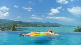 Ontspannende mens in blauwe borrels die op matras in water zwembad drijven stock footage