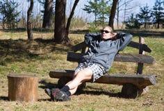 Ontspannende mens op houten bank Stock Afbeeldingen