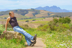 Ontspannende mens tegen landbouwbedrijf en berg Royalty-vrije Stock Afbeelding