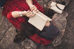 Ontspannende ogenblik Aziatische toerist die een boek op rots lezen royalty-vrije stock foto's