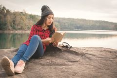 Ontspannende ogenblik Aziatische toerist die een boek op rots lezen stock afbeeldingen