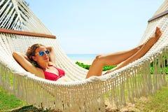 Ontspannende Vrouw in een hangmat op een tropisch strand Royalty-vrije Stock Afbeeldingen