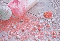 Ontspanning en behandelingsachtergrond met badbom, met de hand gemaakte zeepbar, zeeschelpen en aromatherapy zout Royalty-vrije Stock Afbeeldingen