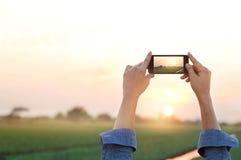Ontspant de landelijke prairie van de vrouwenfotografie in zonsondergang, tijd royalty-vrije stock afbeeldingen