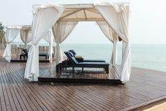 Ontspant het strand voor dubbele leer stoelen binnen een tent die s onder ogen zien Stock Foto