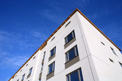 Ontsproten van een voorzijde van een nieuw gebouw bij blauwe hemel stock afbeelding