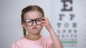 Ontstemd meisje die glazen, ongemakkelijke schouwspelkaders, slechte lens opstijgen stock videobeelden