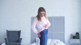 Ontstemde vrouw die lichaam na gewichtsaanwinst bekijken stock videobeelden