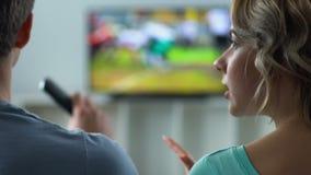 Ontstemde vrouw die met echtgenoot het letten op voetbal op TV ruzie maken, conflict stock video