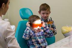 Ontvangst bij de tandheelkunde Een kleine jongen legt op de laag en de holding beschermende glazen royalty-vrije stock afbeelding