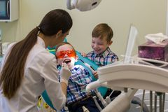 Ontvangst bij de tandheelkunde Het glimlachen weinig jongen legt op de laag in beschermende glazen stock afbeeldingen