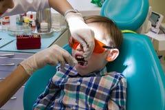 Ontvangst bij de tandheelkunde De tandarts onderzoekt de mondholte royalty-vrije stock foto