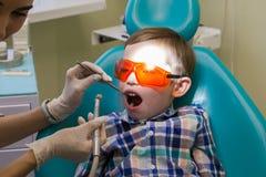 Ontvangst bij de tandheelkunde De tandarts onderzoekt de mondholte en bereidt de machine voor royalty-vrije stock fotografie