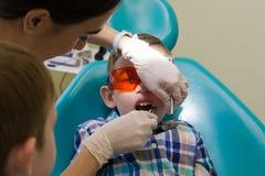Ontvangst bij de tandheelkunde De tandarts onderzoekt de mondholte Jongenszitting in beschermende oranje glazen royalty-vrije stock afbeeldingen