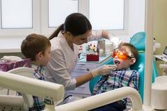 Ontvangst bij de tandheelkunde Twee jongens in het kabinet Een kleine jongen legt op de laag en zijn broer die hem bekijken stock fotografie