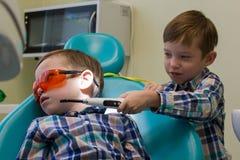 Ontvangst bij de tandheelkunde Twee jongens in het kabinet Een kleine jongen legt op de laag en zijn broer die de lamp houden stock foto