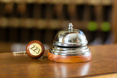 Ontvangst - de klok en de sleutel die van het Hotel op het bureau liggen stock afbeeldingen
