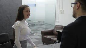 In ontvangstbureau ontmoet de secretaresse bezoeker en escortes aan de werkgever stock video