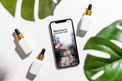 Ontwerp van het smartphonescherm, Toepassing van schoonheidsmiddelen online Witte serumfles en roomkruik, model van het merk van  royalty-vrije stock fotografie