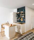 Ontwerp van moderne huiskeuken in de zolder en rustieke stijl Zwarte muur met planken, dienbladen, kruiken, mokken Ijskast, die t stock foto