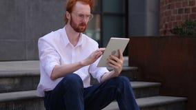 Ontwerper Browsing op Tablet terwijl het Zitten op Bureautreden stock footage