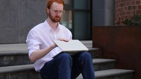 Ontwerper Closing Laptop terwijl het Zitten op Treden van bureau royalty-vrije stock fotografie