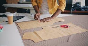 Ontwerper die stuk die van materiaal met het krijt van de kleermaker schetsen met de hand gemaakte kleren maken stock video