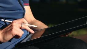 Ontwerper het typen bericht op Tablet bij park stock video