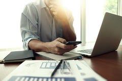Ontwerperhand het werken en slimme telefoon en laptop op houten bureau Stock Afbeeldingen