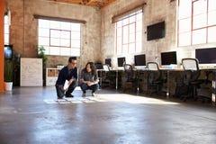 Ontwerpers die Lay-out op Vloer van Modern Bureau plannen Stock Foto