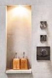 Ontworpen badkamers met ruwe concrete muur die met fles s wordt verfraaid Stock Afbeelding