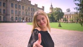 Ontzagwekkend Kaukasisch blondemeisje in motie op stadsachtergrond en het aantonen als gebaar met leuke glimlach openlucht stock videobeelden
