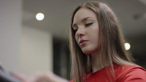 Ontzagwekkend meisje in rood overhemd en blauwe legginspedalen op de hometrainer en watchs tijd in de nieuwe gymnastiek stock video