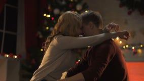 Ontzagwekkend teder paar die dichtbij fonkelende Kerstboom, het vieren vakantie koesteren stock videobeelden