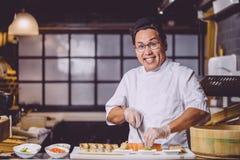 Ontzagwekkende glimlachende Chinese mens die mes gebruiken om sushi in stukken te snijden royalty-vrije stock afbeeldingen
