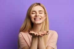 Ontzagwekkende speelse vrolijke jonge vrouw die een kus over blauwe achtergrond verzenden stock fotografie