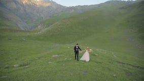 Onvergetelijke romantische gang van de bruid en de bruidegom op hun huwelijksdag onder de mooiste bergen van Georgië stock videobeelden