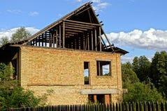 Onvolledig huis van bruine baksteen en houten dak onder de groene bomen achter de omheining stock fotografie