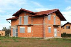 Onvolledig nieuw huis met nieuwe daktegels, goten, deuren en vensters royalty-vrije stock foto