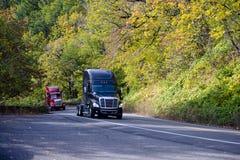 Сonvoy of two modern trаctors semi trucks on green road Stock Photos